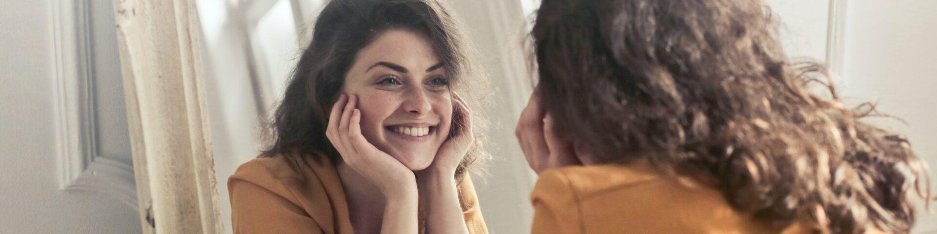vrouw kijkt in de spiegel met zelfcompassie